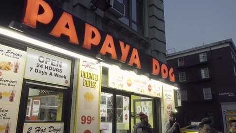 NEW YORK - DEC 6, 2015: famous Papaya Dog fast food frankfurters in the West Village at night with bright glowing red sign in NYC 4K. 6th Ave is also known as Avenue of the Americas.