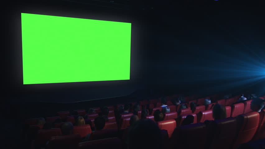 Group of people are watching a green screen mock-up film screening in a movie cinema theater. Shot on RED Cinema Camera in 4K (UHD).