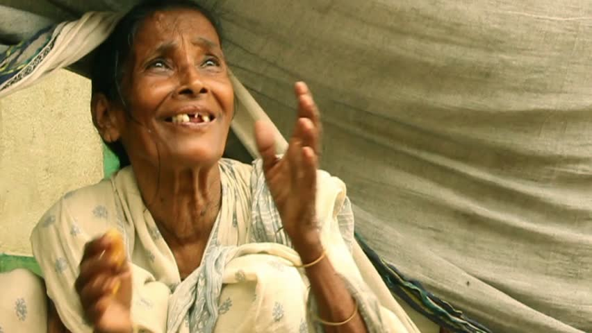 Elderly Indian woman smiles and fold hands in gratitude upon receiving some vegetarian food. She has been put out of home by a big flood | Shutterstock HD Video #13707548