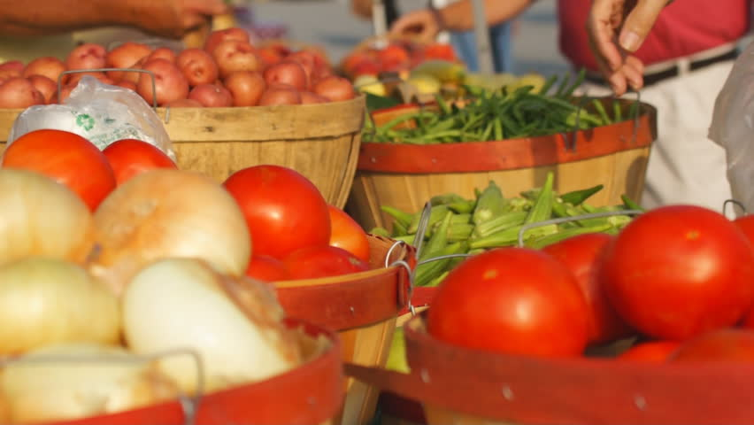 Fresh vegetables being purchased at Farmer's Market.