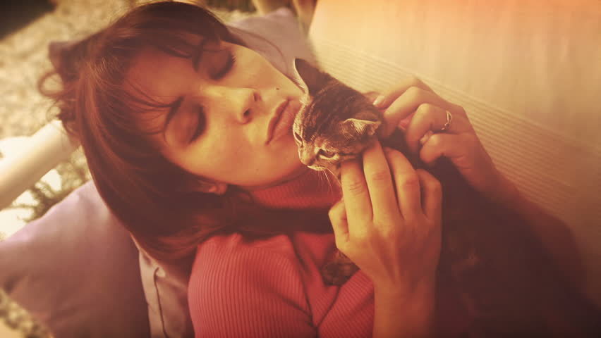 A beautiful girl plays with a kitten on a swing in the garden. Video about love for animals, respect for animals. Video effect with super 8mm. The video looks vintage, approximately 60s. Portrait. | Shutterstock HD Video #13808078