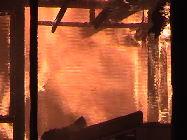 Fire engulfs the inside of a structure with falling debris.