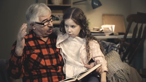 Intelligent grandfather showing his little granddaughter pictures in book and telling interesting facts