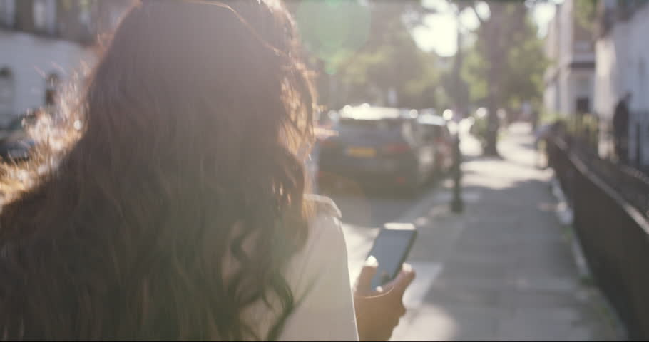 Beautiful Indian woman walking through city living happy lifestyle using smart phone reading social media