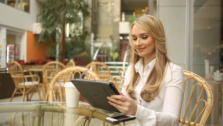 Woman using tablet computer touchscreen in cafe drinking coffee | Shutterstock HD Video #13833488