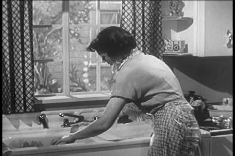 CIRCA 1950s - A housewife washes dishes by hand in the 1950s.