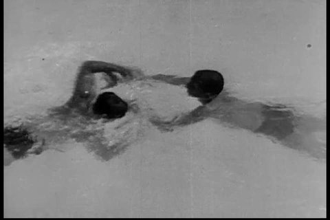 CIRCA 1930s - The wrist lock and back headlock release grips in 1933, shown by a U.S. swimmer and lifeguard on a drowning victim.