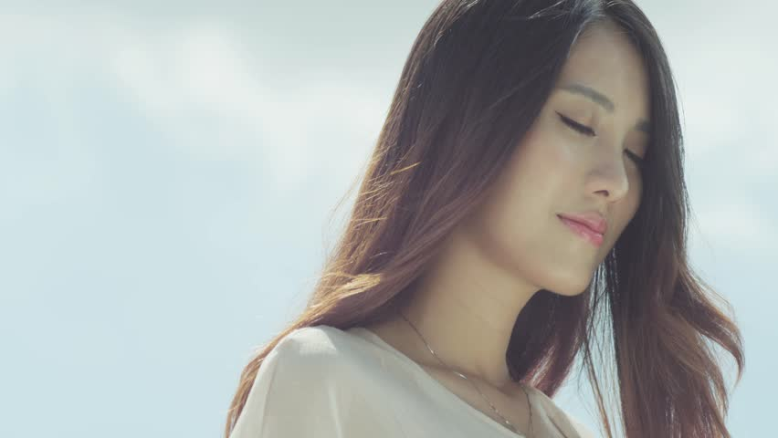Closeup of a young Chinese woman enjoying sunshine in nature