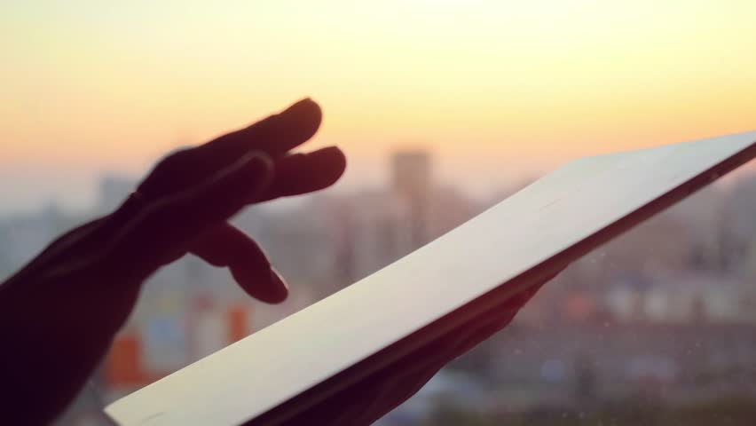 Businesswoman hand using tablet in the office with glass window over city at beautiful sunset | Shutterstock HD Video #13942568