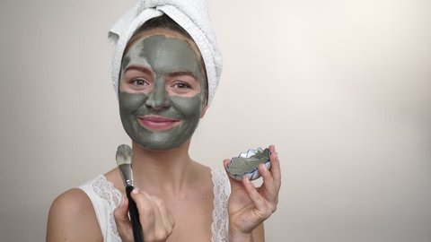 Skin care. Woman applying with brush clay mud mask to her face studio shot. Girl taking care of oil complexion. Beauty treatment. 4K ProRes HQ codec