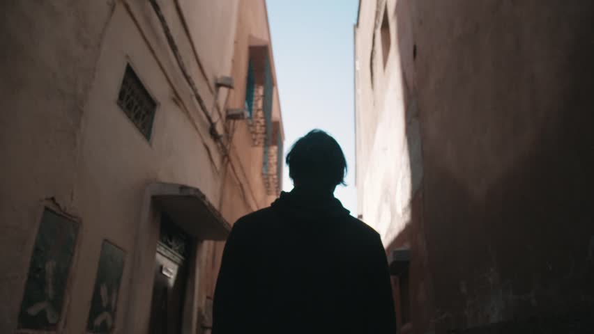 Figure walking through a tight Moroccan alley way  | Shutterstock HD Video #13949078