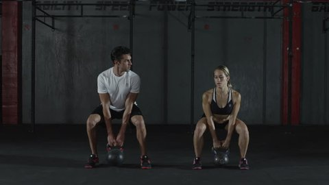 A man and woman doing kettle bell exercising and lifts, squats - kettlebell - fitness / crossfit / exercise / workout