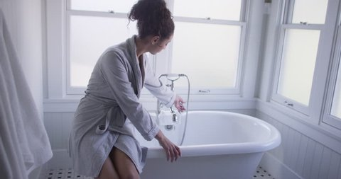 Charming young woman sitting on bathtub testing water
