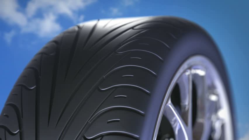 Car wheel with sport tire rotating closeup. HD loopable. Blue sky in the background | Shutterstock HD Video #14012810