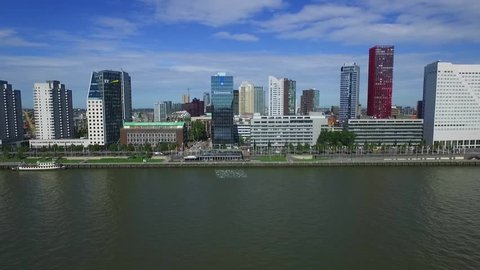 Aerial shot in Rotterdam, Europe, flying over the river towards the city center on a sunny summer day.