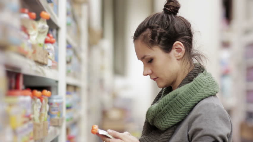 Young woman chooses baby food in the supermarket | Shutterstock HD Video #14051816