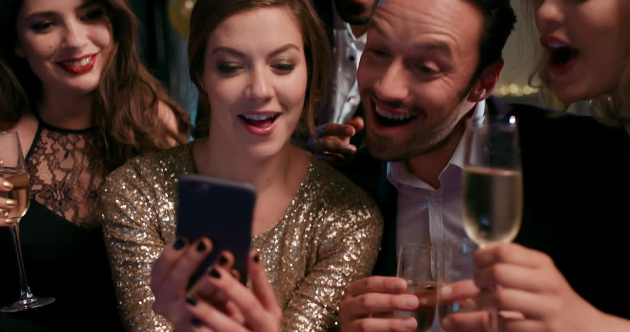 Sexy friends laughing at funny viral video online watching social media on smart phone at glamorous fashion party drinking champagne   Shutterstock HD Video #14075978