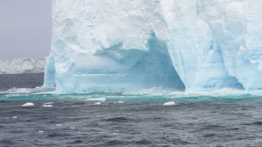 Large tabular iceberg with carved arches in rough seas of Drake Passage, Antarctica.