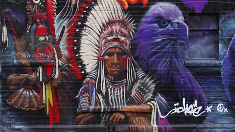 BRISTOL - January 23: Woman Walks Past Intricate Street Art / Graffiti of Native American Indian in Stoke's Croft, on January 23rd 2016 in Bristol England.