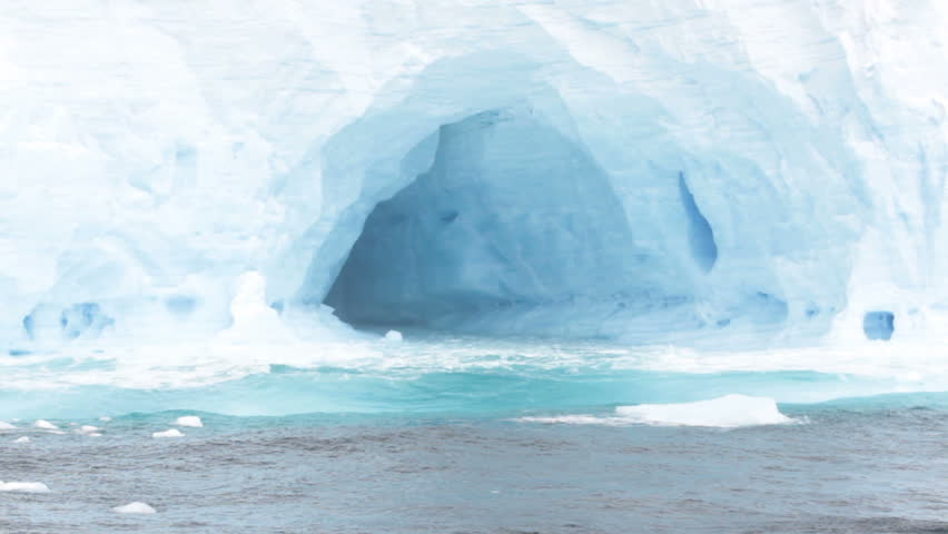 Close up of arches in large tabular iceberg in rough seas of Drake Passage near Antarctica on stormy day.