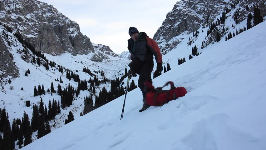 Tourist sat down to rest on his backpack on a snowy mountain trail