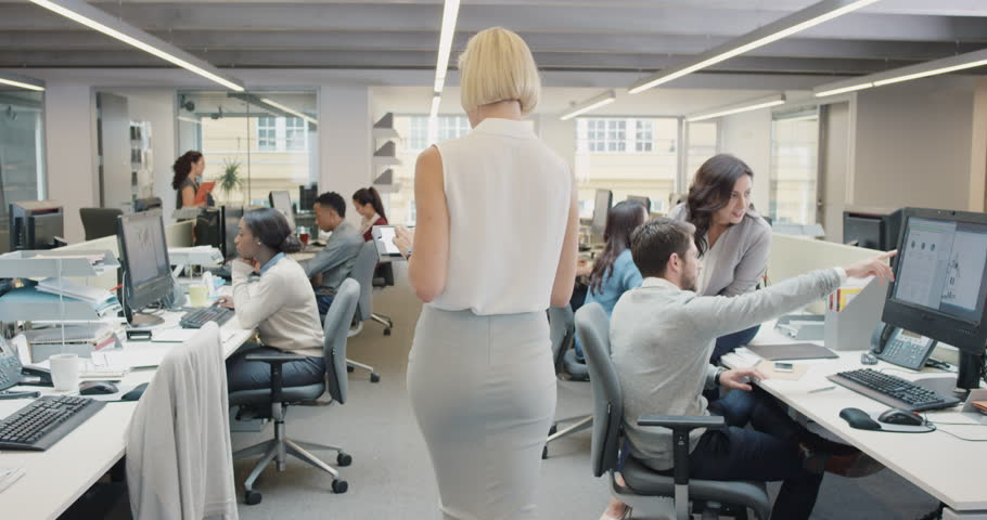 Business woman using digital tablet walking through busy office touchscreen display manipulating 3d shape