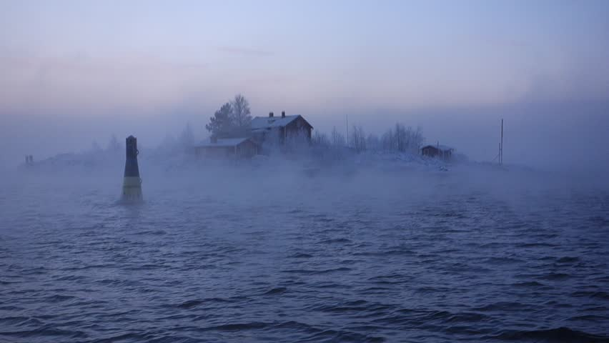 Snow covered small island in the middle of the sea smoke on an extremely cold morning in Helsinki, Finland archipelago and a navigation buoy with waves in the Baltic sea on 5 January 2016.