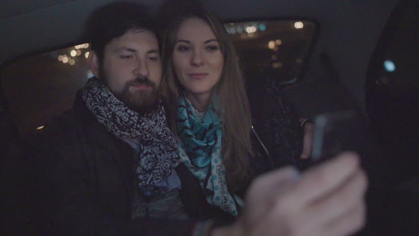 Young adult couple making selfie and kisses in a car at night
