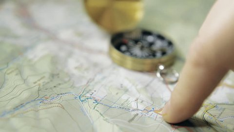 HD Dolly shot of men's finger planning hiking trip on a map with compass. Shot with motorized dolly and Canon 5Dmk2.