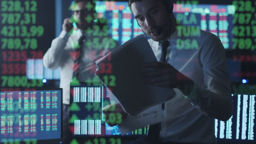 Stockbroker in white shirt is talking on the phone while working in a dark monitoring room with display screens. Shot on RED Cinema Camera in 4K (UHD).