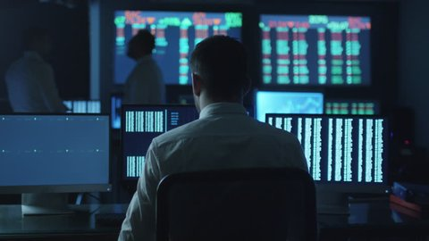 Stockbroker spotted a positive trend in trading charts while working in a dark monitoring room with display screens. Shot on RED Cinema Camera in 4K (UHD).