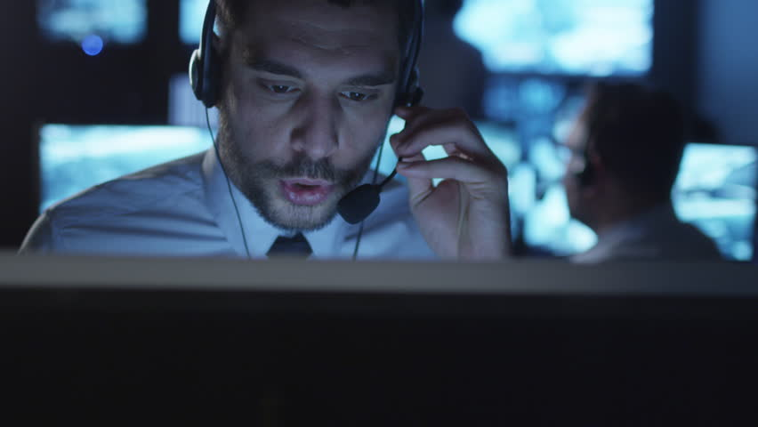 Happy technical support specialist is drinking coffee while working on a computer in a dark monitoring room filled with display screens. Shot on RED Cinema Camera in 4K (UHD).