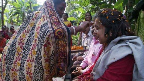 Baruipur, India - CIRCA 2013 - Man and women receiving the bindi at women meeting