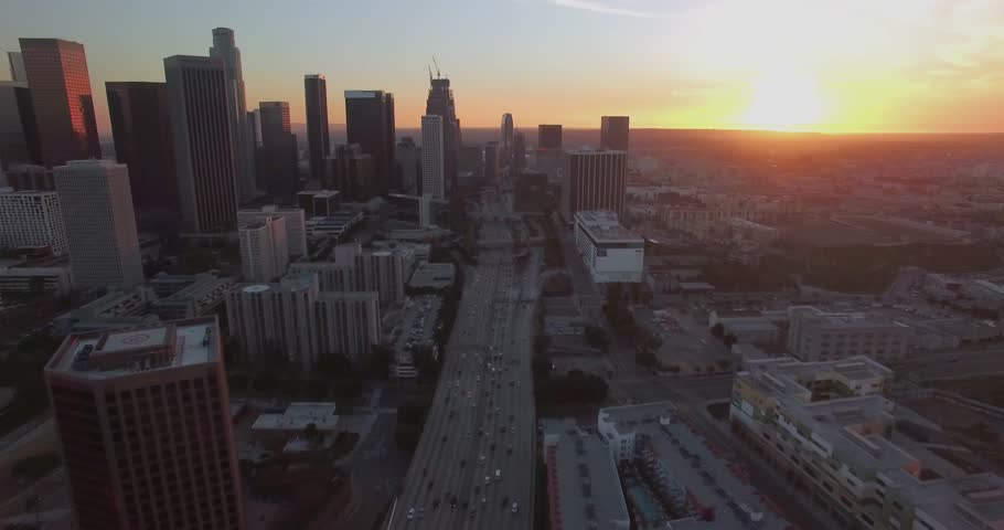 Above Downtown Traffic / Aerial 4K footage flying above downtown Los Angeles traffic during sunset/sunrise with clear skies and minimal traffic.