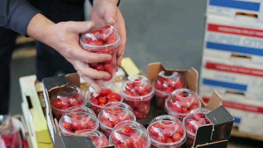A worker opens a container of cherry tomatoes and checks their condition after transportation. Box contains a lot of containers. Order for carriage for eat. Distributor imported for resale. Close up | Shutterstock HD Video #14223668
