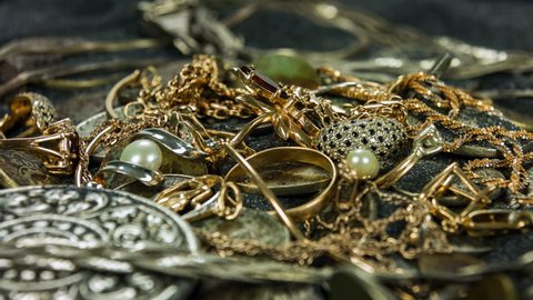 Old coins and gold treasures in a dark sand close-up rotation.