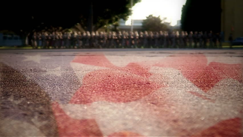 Very low shot of American flag painted on concrete, Marines out of focus marching in background