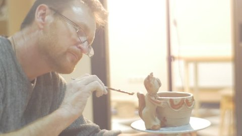 Middle Aged Man in Glasses, Man with Beard is Glazing A Pot, Painting by Brush Attentively, Clay cat figurine is Holding a Pot,People are Making a Gifts from a Clay, people are learning a pottery,