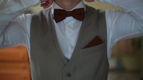 Man in the white shirt correcting bow-tie.
