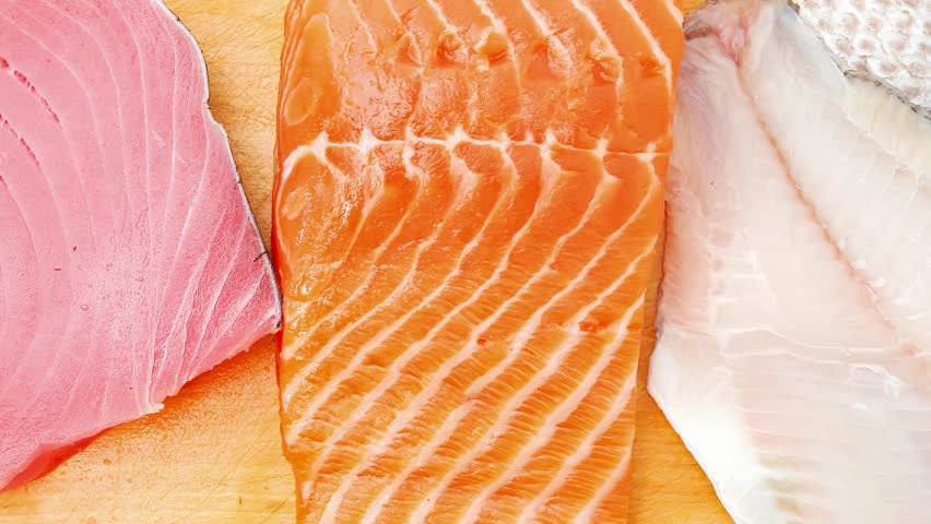 Raw set of sea fish food : salmon red tuna and sole fish chunks served on wooden plate 1920x1080 intro motion slow hidef hd | Shutterstock HD Video #14286718