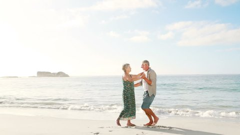 Retired old couple dancing together on the beach