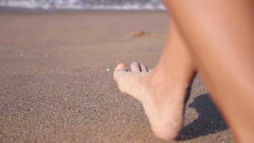 Woman Feet Walking on Beach Leaving Footprints in Sand