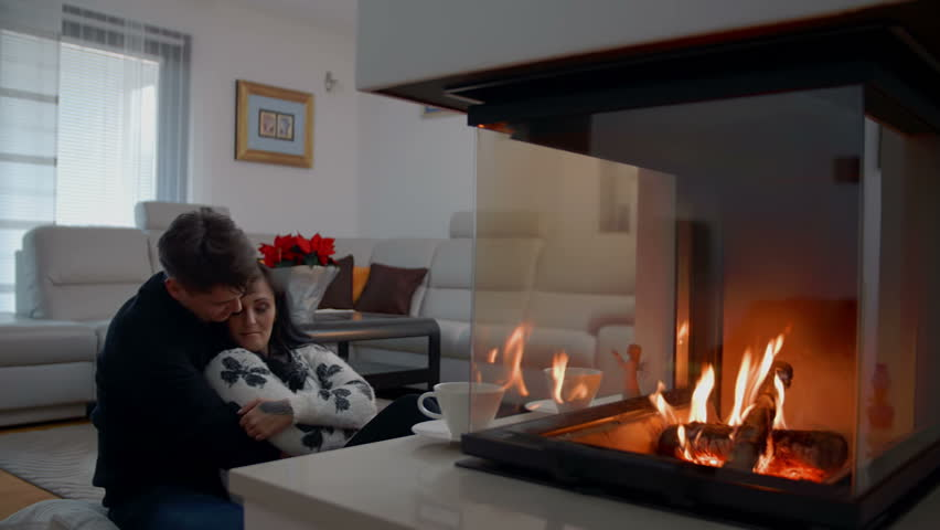 In this video, we can see that a young couple is cudding in front of a fire-place in the living room of their house. They are also drinking tea. They look adorable. Wide-angle shot.