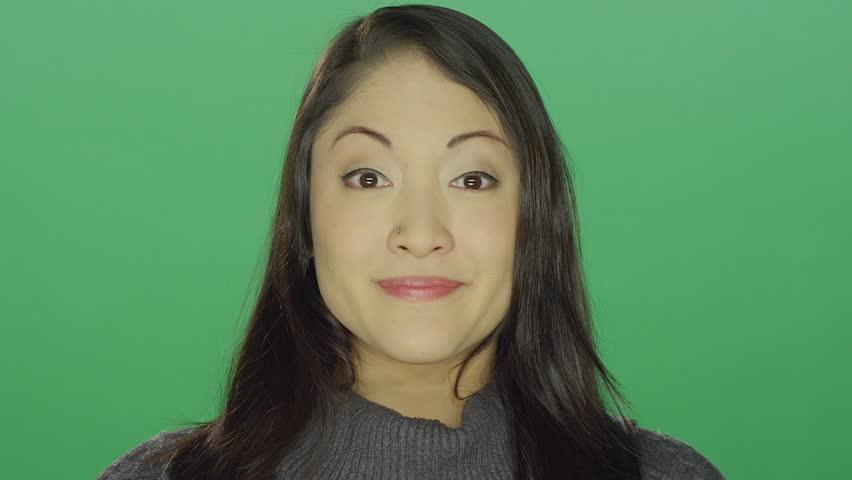 Beautiful young asian woman smiling, on a green screen studio background | Shutterstock HD Video #14360518