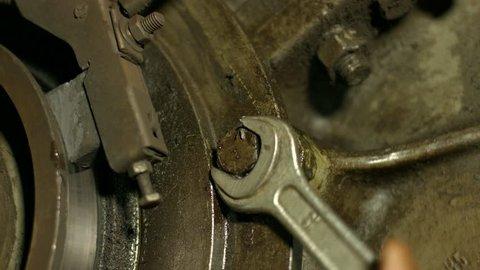 Engine repair. Mechanic tightening the screws. Repair of equipment. Mechanic repairing a car.