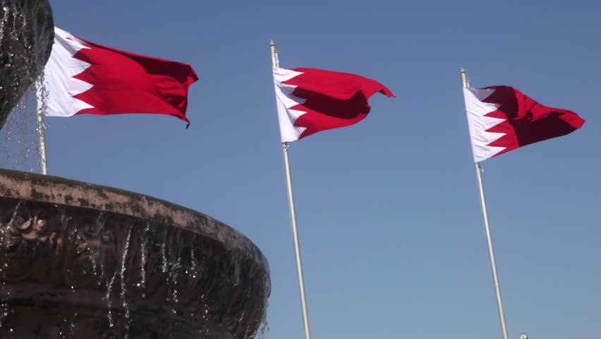 Bahrain Flags waving behind a fountain in Manama, Bahrain