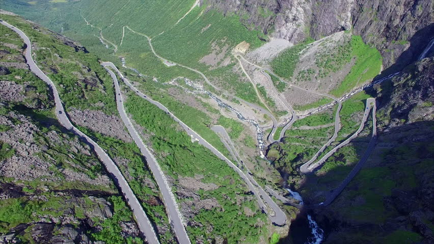 Aerial view of hairpin bends of Trollstigen mountain pass in Norway on sunny summer day, one of the most beautiful roads in the world, major tourist attraction. Aerial 4k Ultra HD.