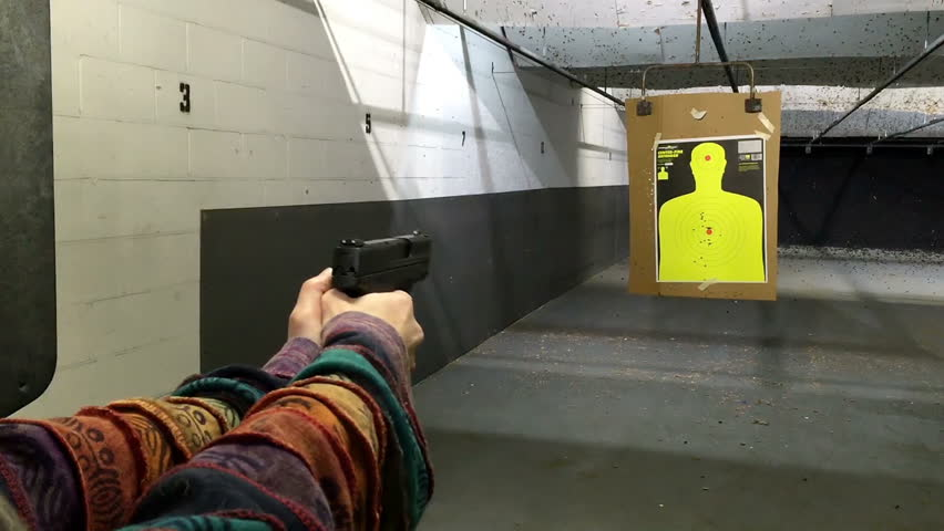 A woman with a 9mm handgun practices target shooting at an indoor range