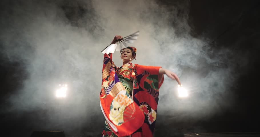 4K beautiful Japanese geisha dancing on stage and posing for the camera,the smoke in the background, slow motion #14442808