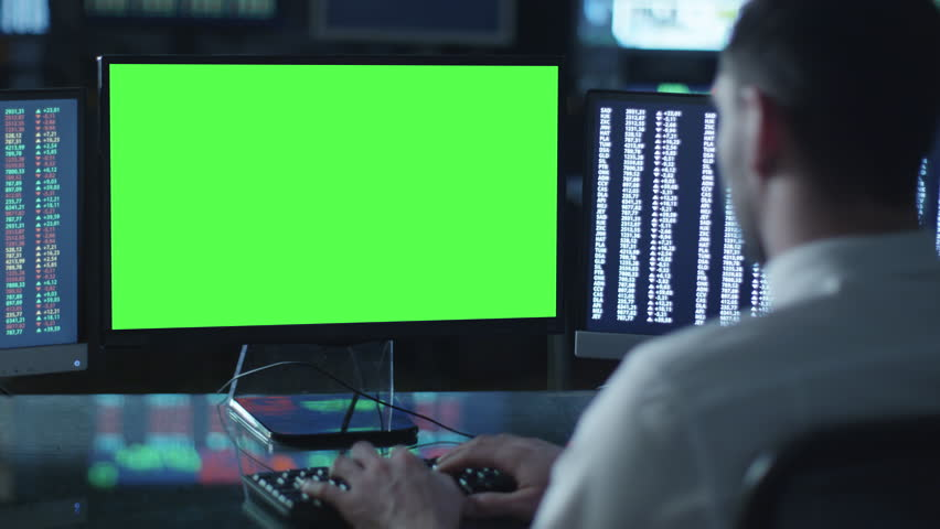 Man is working on a computer with mock-up green screen in a dark office filled with displays. Shot on RED Cinema Camera in 4K (UHD). | Shutterstock HD Video #14453866